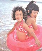 two happy girls playing in float in ocean