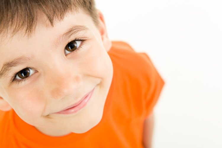 smiling young boy looking up at camera with big eyes
