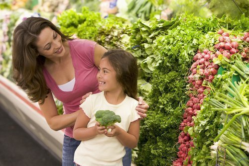 Smiling mother and daughter in front of produce section