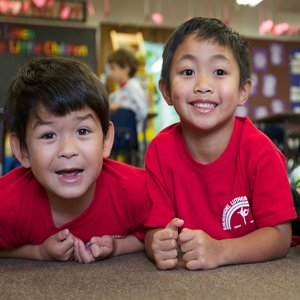 Two smiling boys in red school uniform shirts