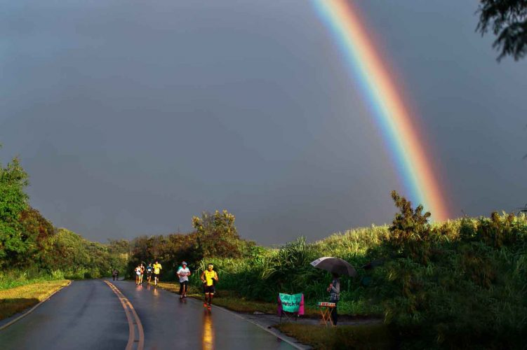 Runners on wet road with strikingly beautiful rainbow